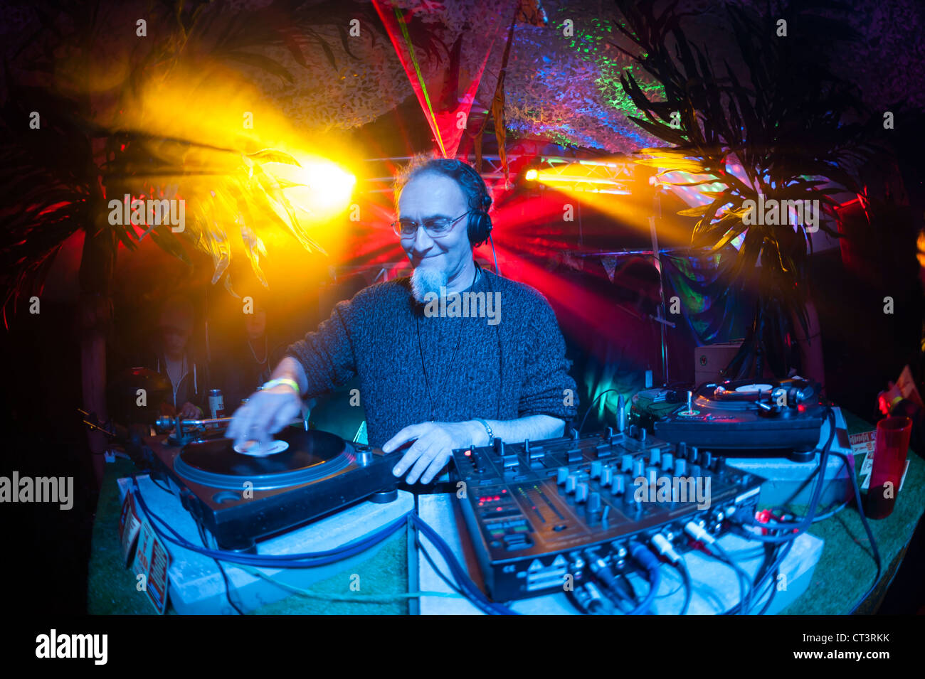 A middle aged older person man DJ'ing at The Rare One music dance party event festival, Wales UK - Stock Image