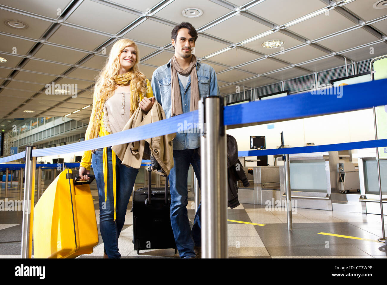 Couple rolling luggage in airport - Stock Image