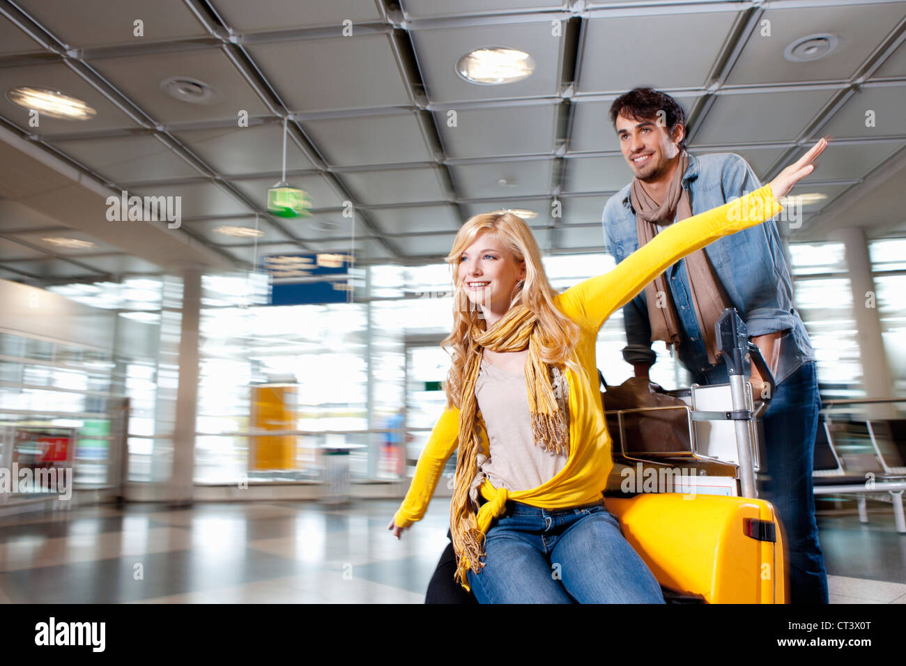 Couple playing with luggage in airport - Stock Image
