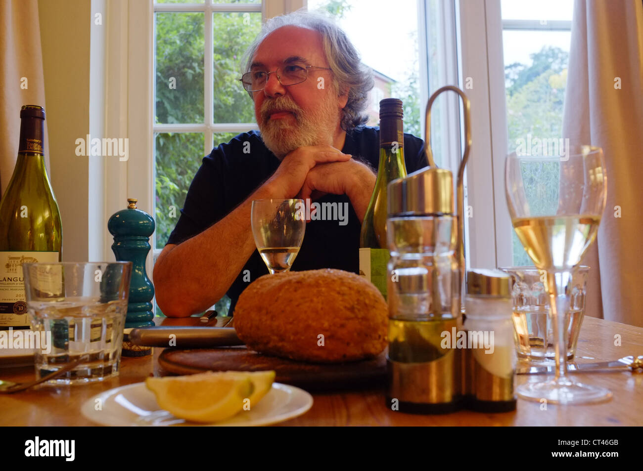 A bon viveur seated at a dining table - Stock Image
