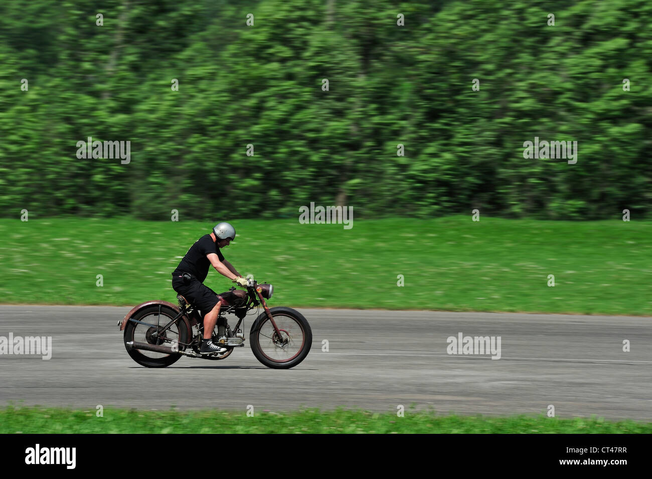 A motorcyclist travelling along a road but not looking where he is going. Motion blur on wheels and background - Stock Image
