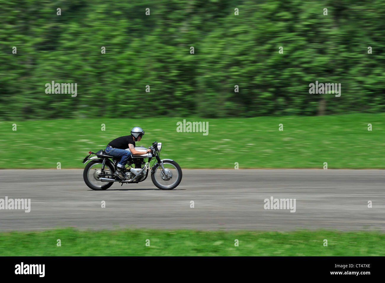 A motorcyclist travelling at high speed. Motion blur on wheels and background Stock Photo