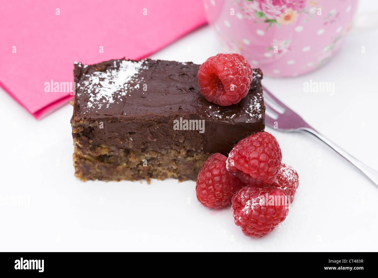 A slice of raw chocolate tart with raspberries. - Stock Image