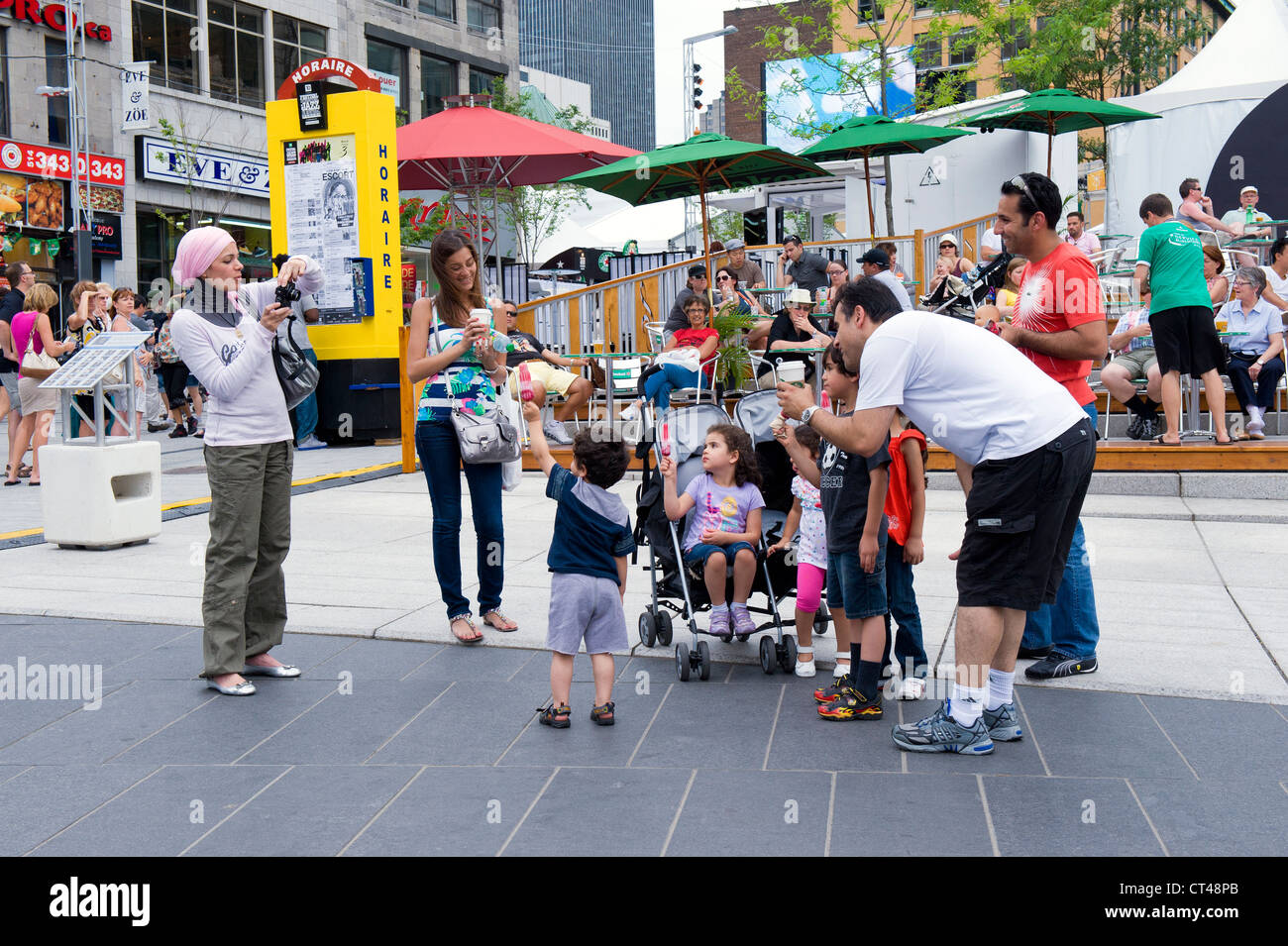 Woman taking a family picture with a digital camera in Montreal during the Jazz Festival. - Stock Image
