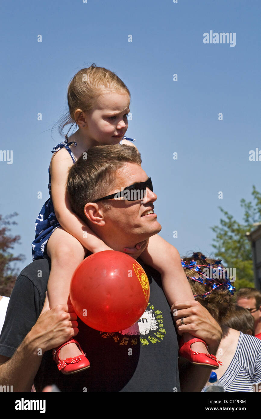 A young girl riding piggy back on her father's shoulders on a downtown street - Stock Image