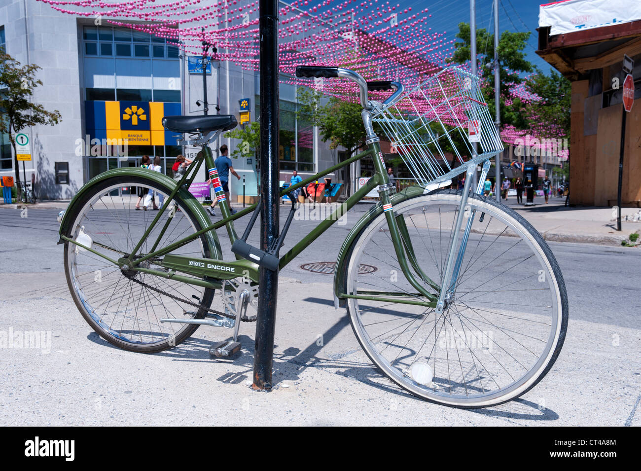 Green bicycle locked to a post in the Gay village , Montreal, province of Quebec, Canada. - Stock Image