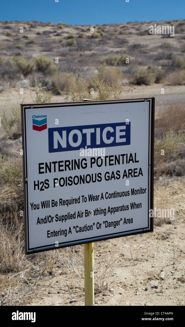 A sign warns of hydrogen sulfide gas near an oil and gas field in the southern San Joaquin Valley. - Stock Image