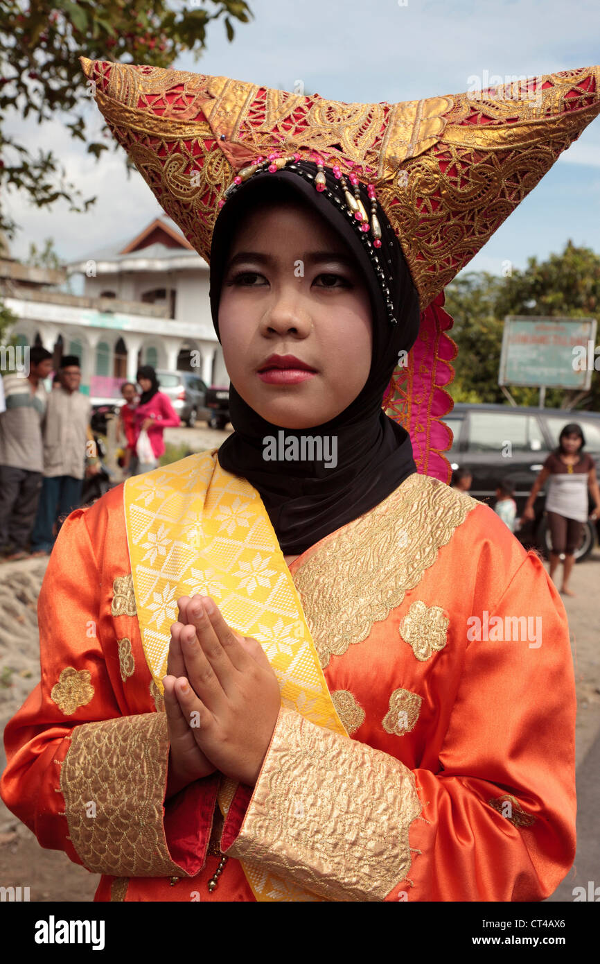Indonesia traditional headdress stock photos indonesia traditional indonesia sumatra padang woman in traditional sumatran dress greeting visitors stock m4hsunfo