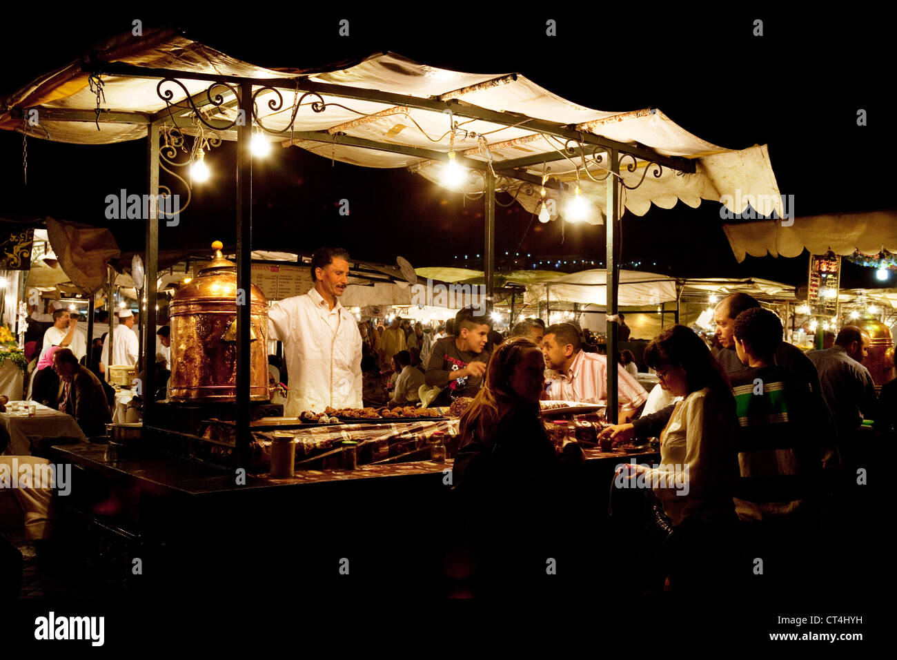 Local people eating street food at food stalls in Djemaa el Fna square at night, Marrakech Morocco Africa - Stock Image