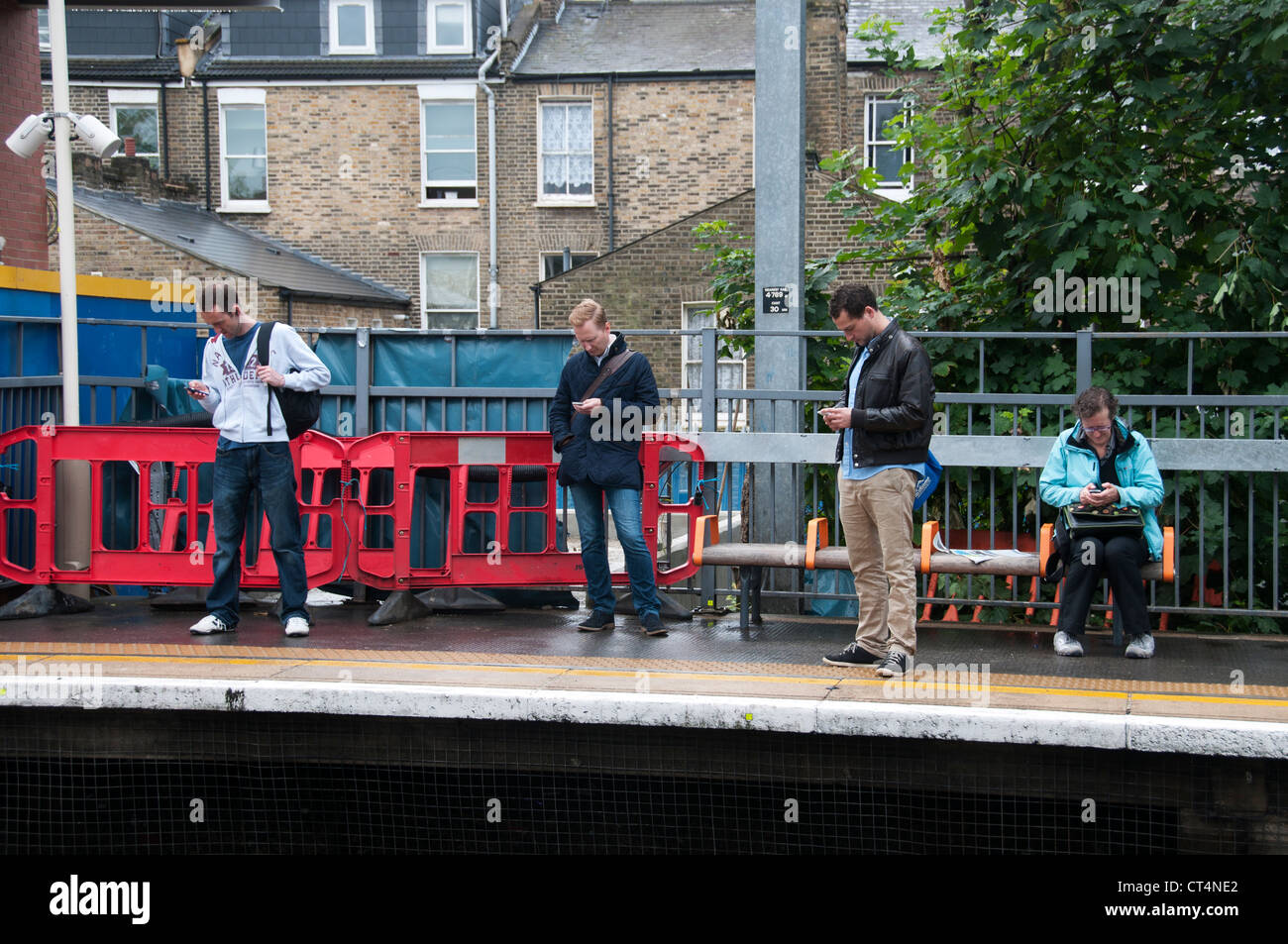 Four people on station platform at Hackney Central, all looking at their mobile phones - Stock Image