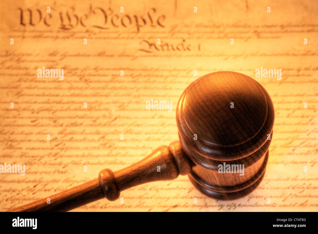 Concept of American justice, gavel on top of constitution in brown tones. - Stock Image