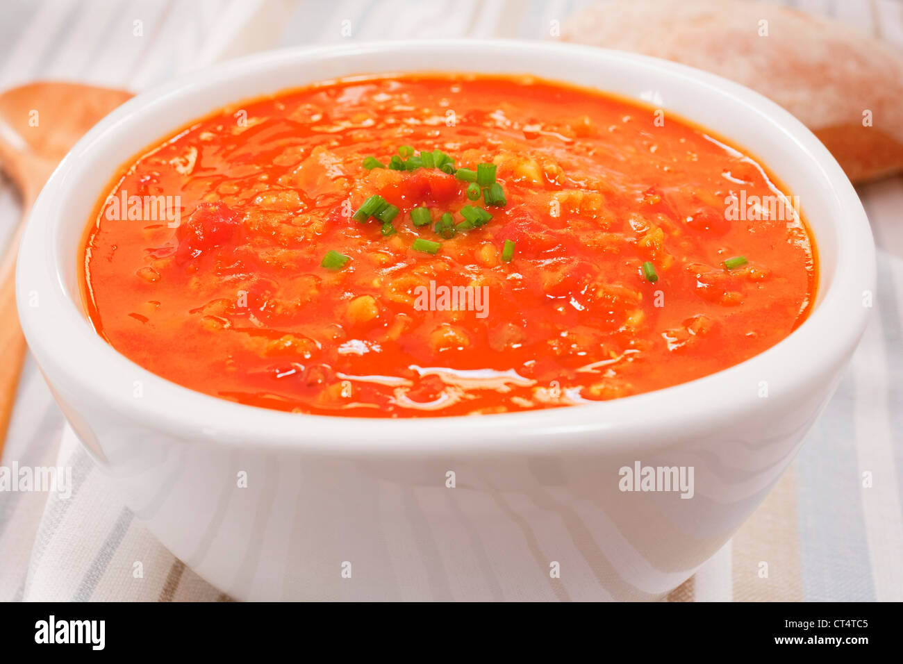 A bowl of lentil and tomato soup garmished with chives. - Stock Image
