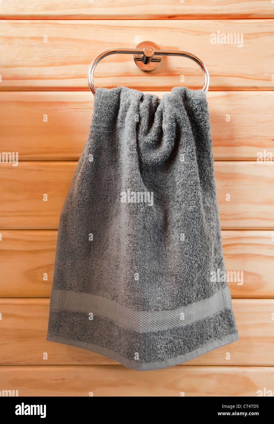 Grey hand towel hanging on chrome towel ring, against a timber wall. - Stock Image