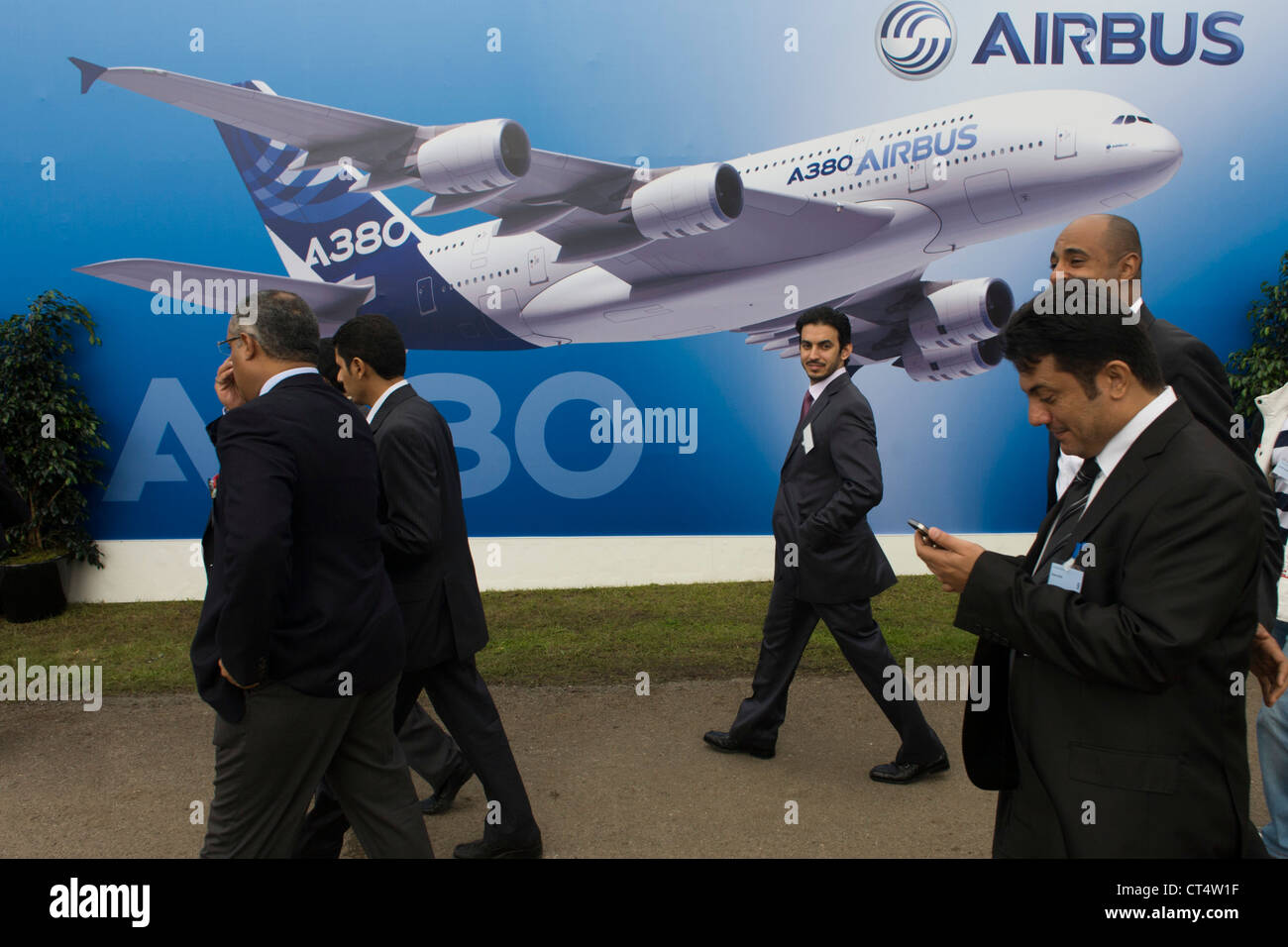 Delegates walk past a mural artwork of an A380 airliner outside one of the EADS company's chalets at the Farnborough - Stock Image