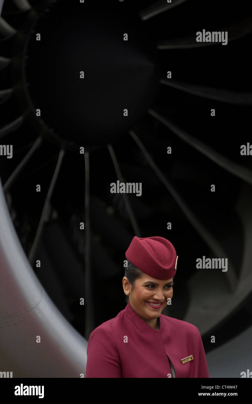 Cabin crew hostess and engine turbofan blades of a Qatar Airways Boeing 787 at the Farnborough Air Show, UK. - Stock Image