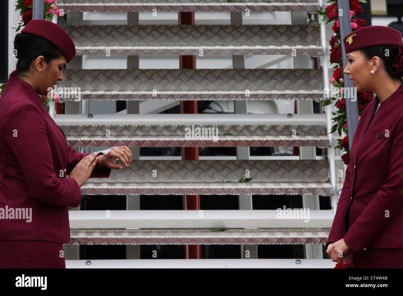 Cabin crew hostess checks her watch at the bottom of steps a Qatar Airways Boeing 787 at the Farnborough Air Show, - Stock Image
