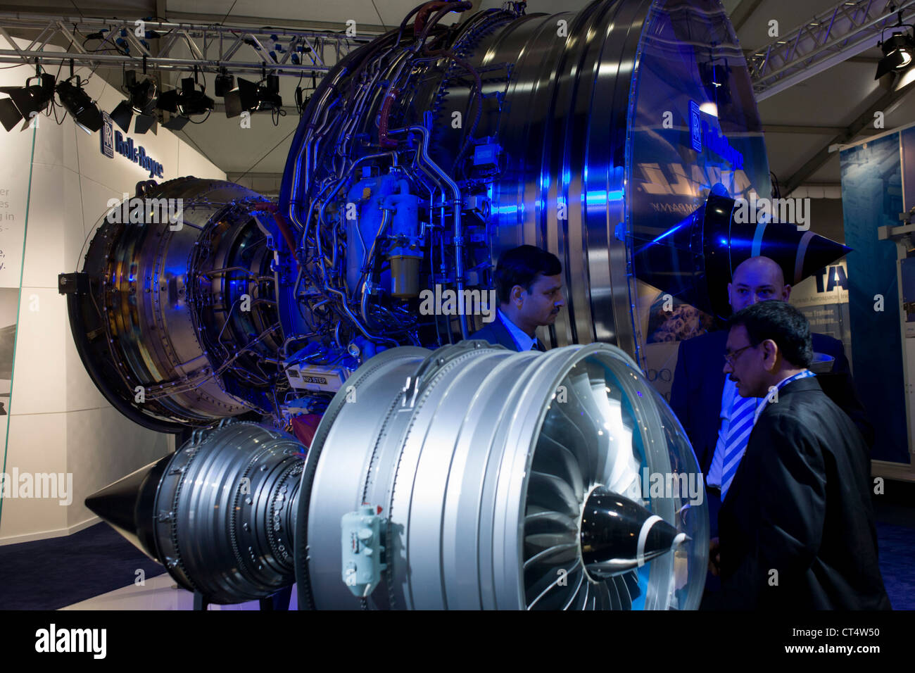 Potential buyers discuss Trent engines with Rolls-Royce employee at the Farnborough Air Show. In one of the main - Stock Image
