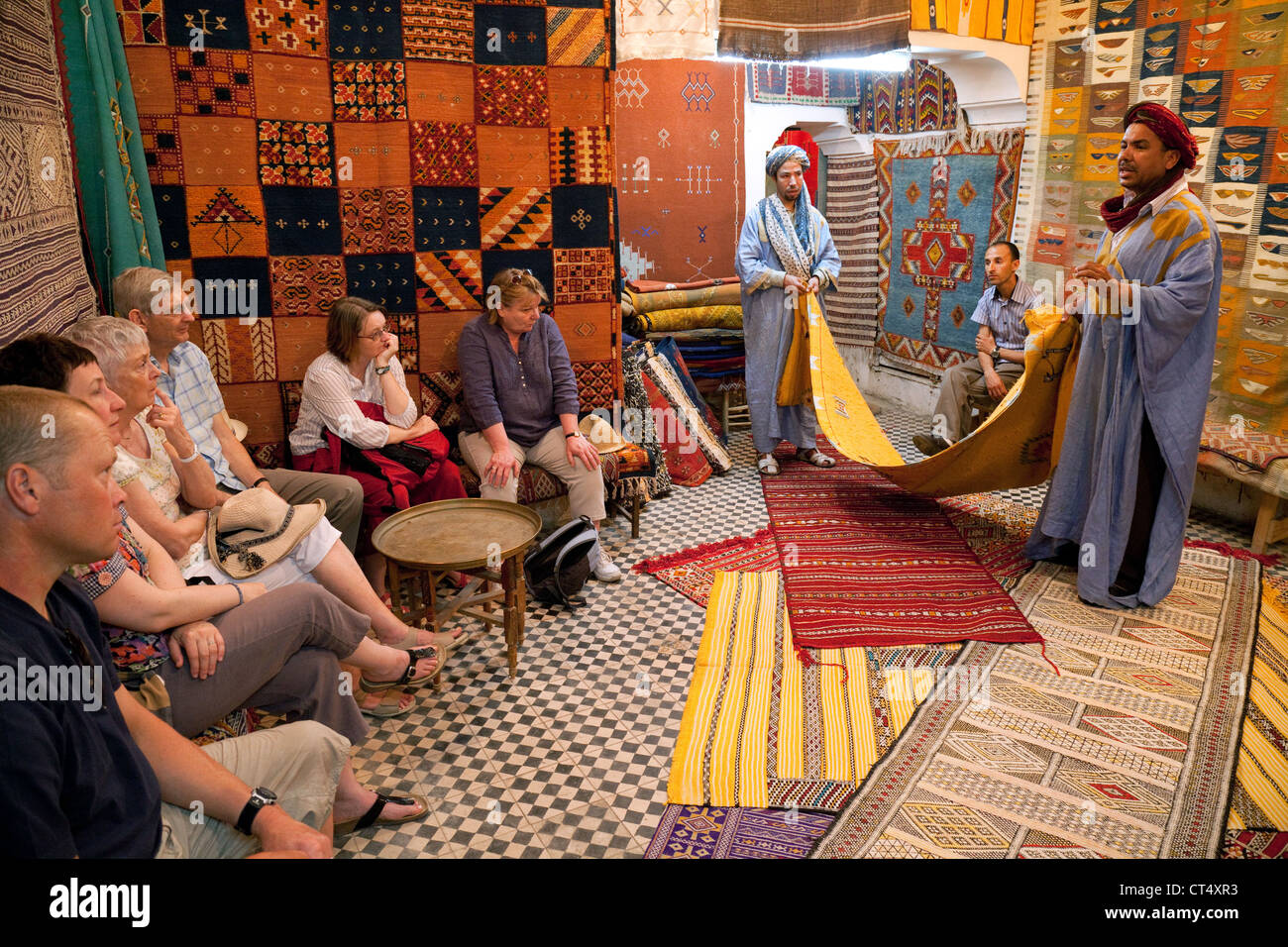 Tourists shopping for carpets in a Berber carpet store, the souk, Taroudant, Morocco Africa - Stock Image