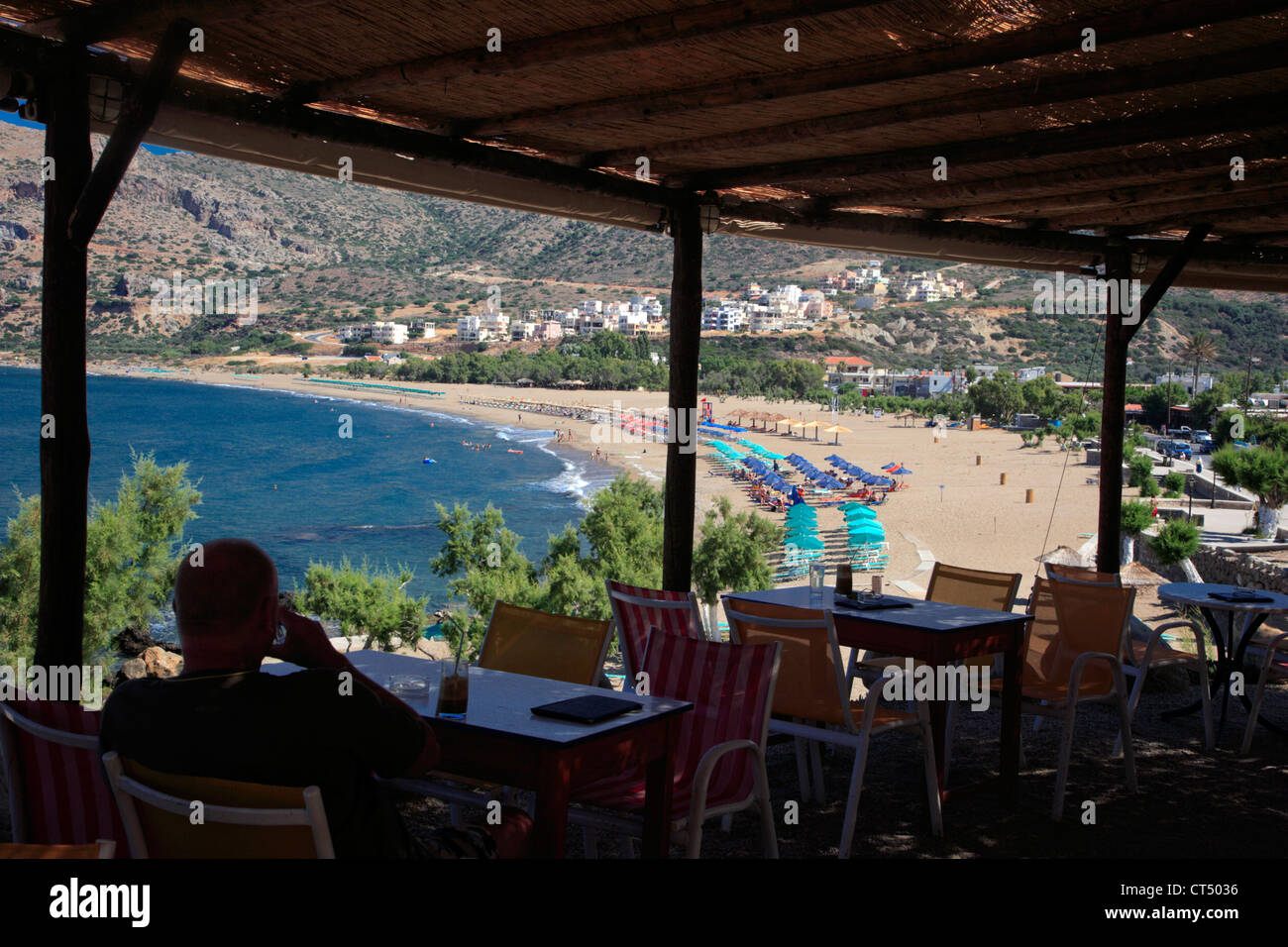 Man sat with drink, enjoying the view from Castello snack bar, Paleochora vilage, Crete, Greece Stock Photo