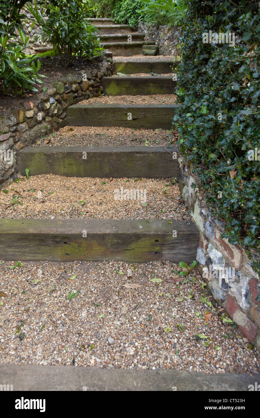 Garden steps leading uphill - Gravel covered steps made from railway sleepers - Stock Image