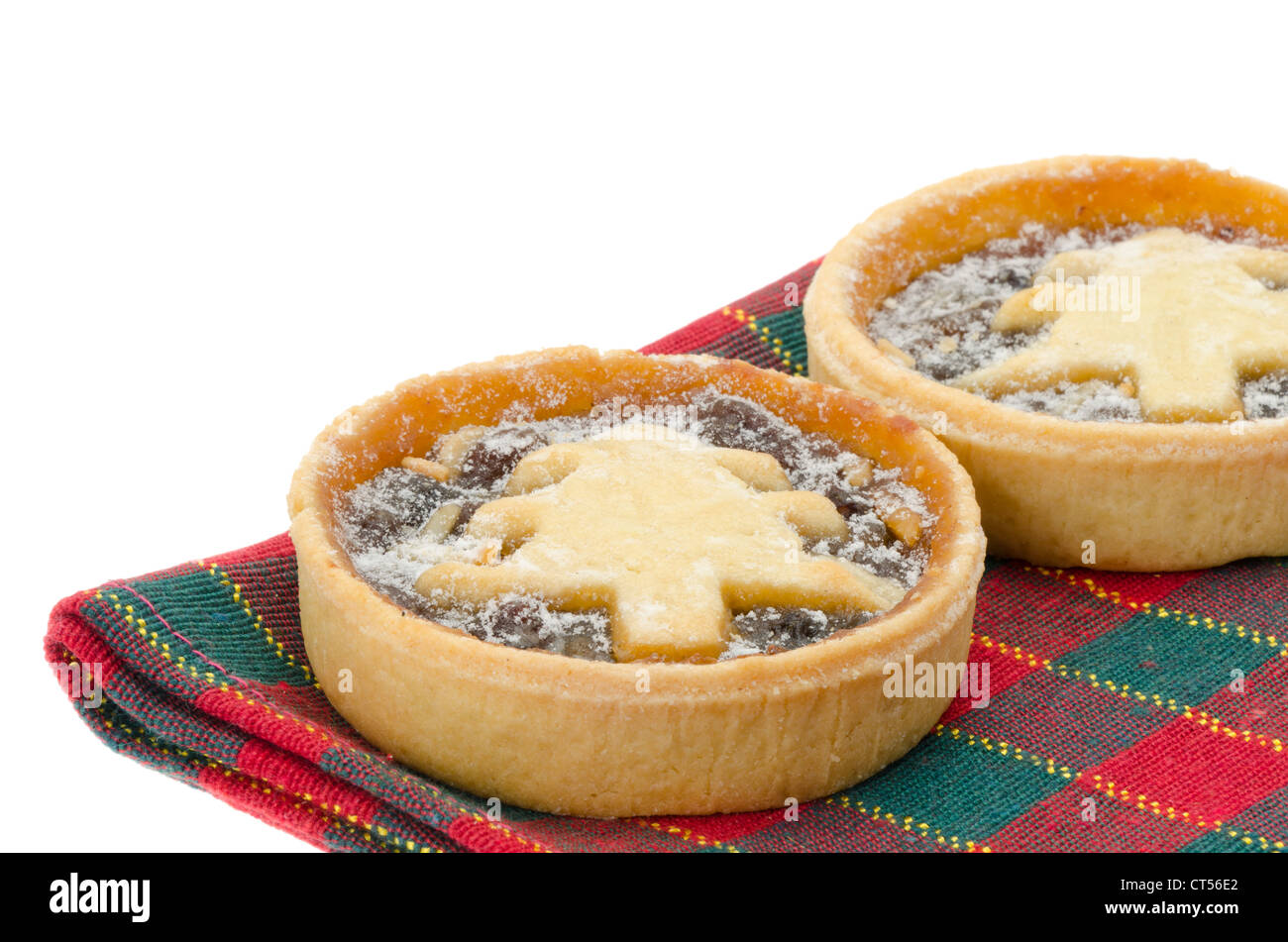 Festive or Christmas mince pie with a shallow depth of field, focus on foreground - studio shot with a white background - Stock Image