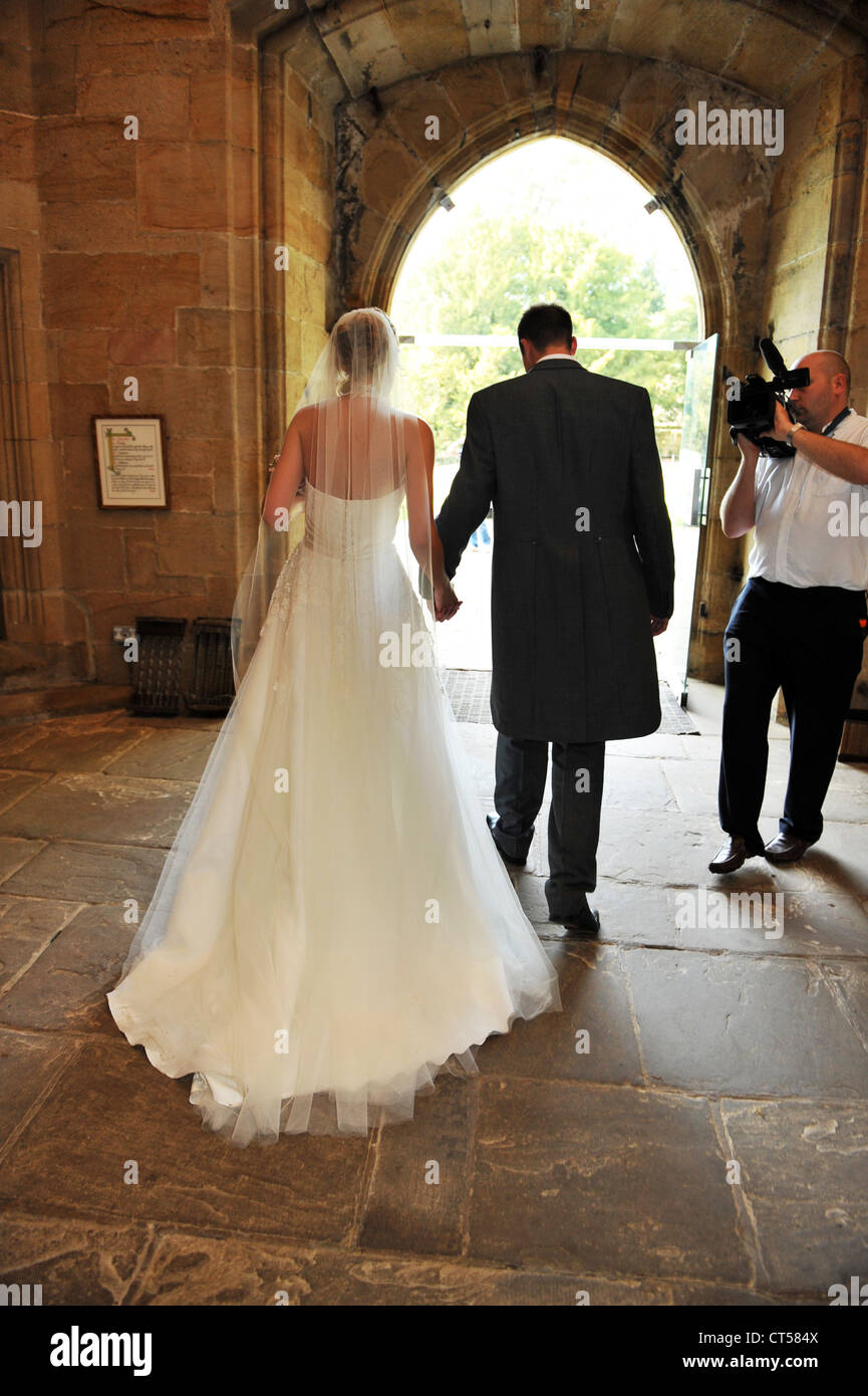 A bride and groom leave the church while being filmed on video. - Stock Image