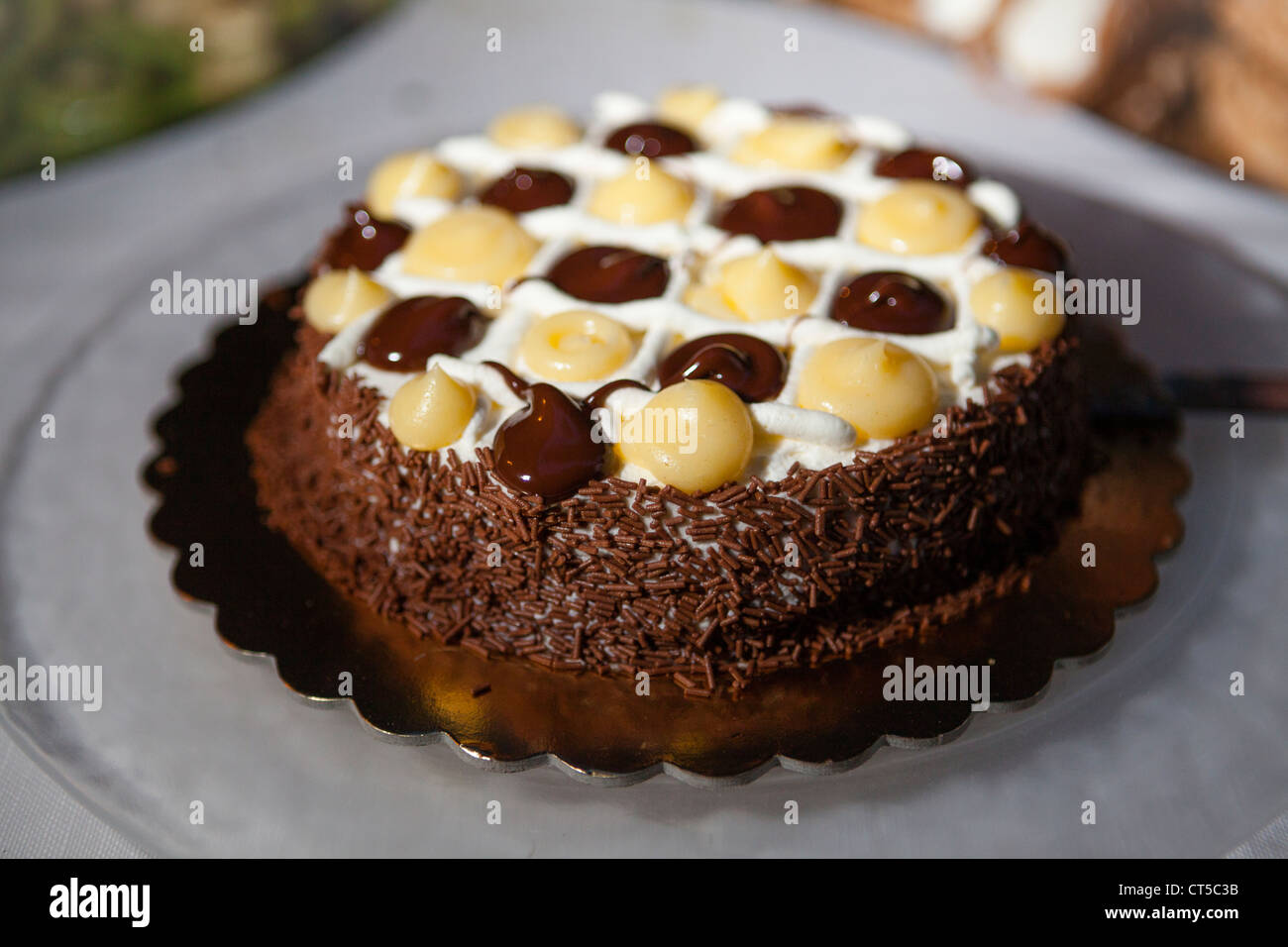 Chocolate cake on plate outdoors - Stock Image