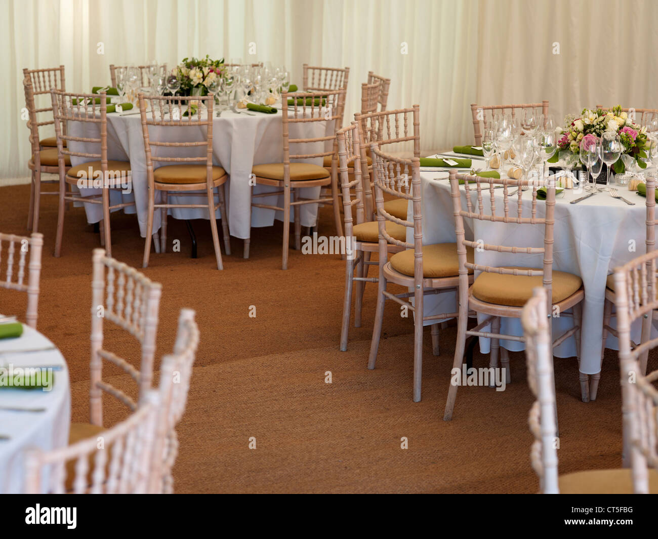 Tables arranged before wedding guests arrive - Stock Image