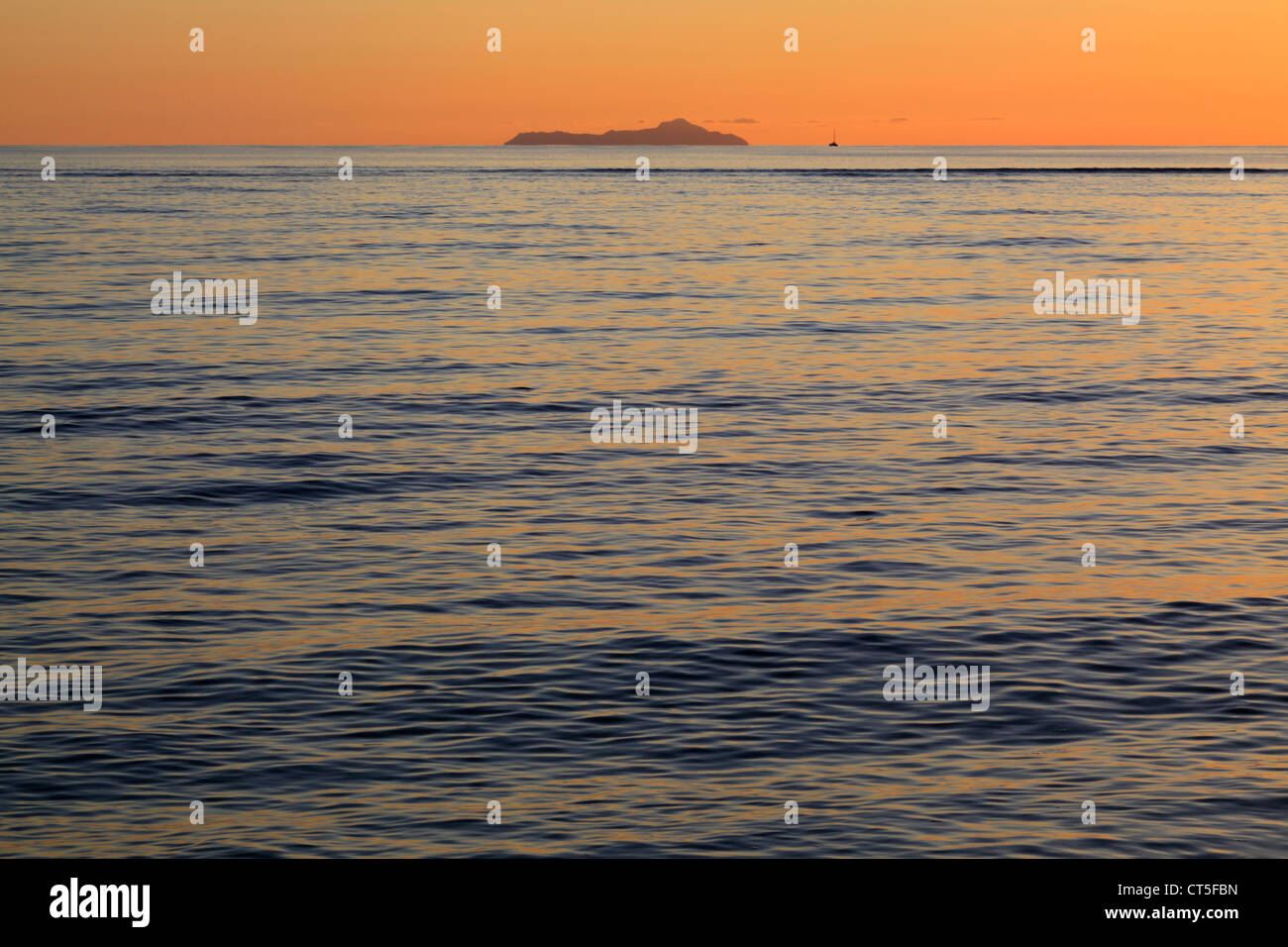Sun sets behind Silhuoette island as seen from La Digue in the Seychelles - Stock Image