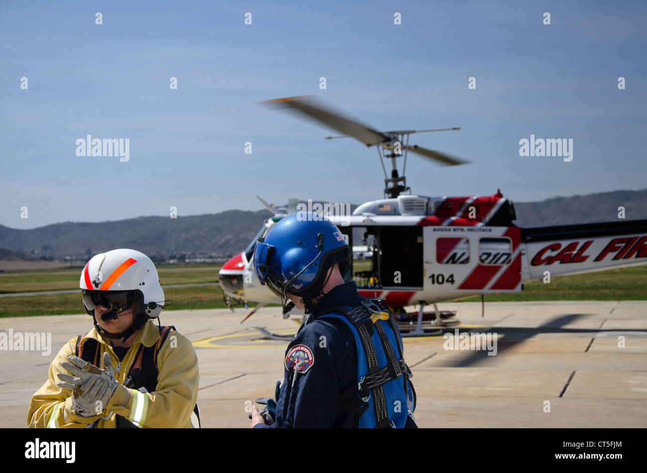 Photo of two members of a Fire Department Helicopter Rescue Team suited up for a training exercise. Helicopter in - Stock Image