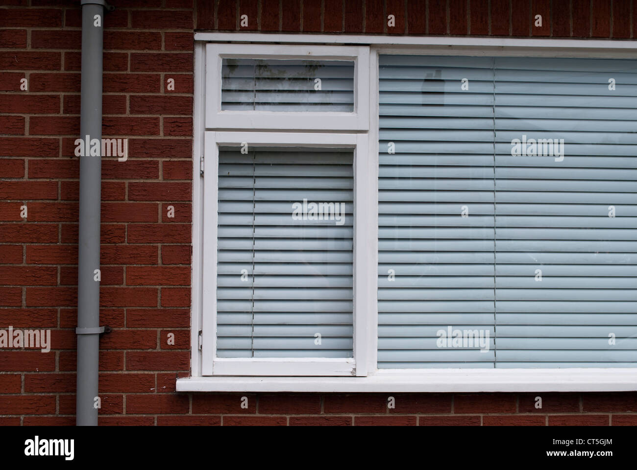 White framed window with closed white venetian blind in red brick ...
