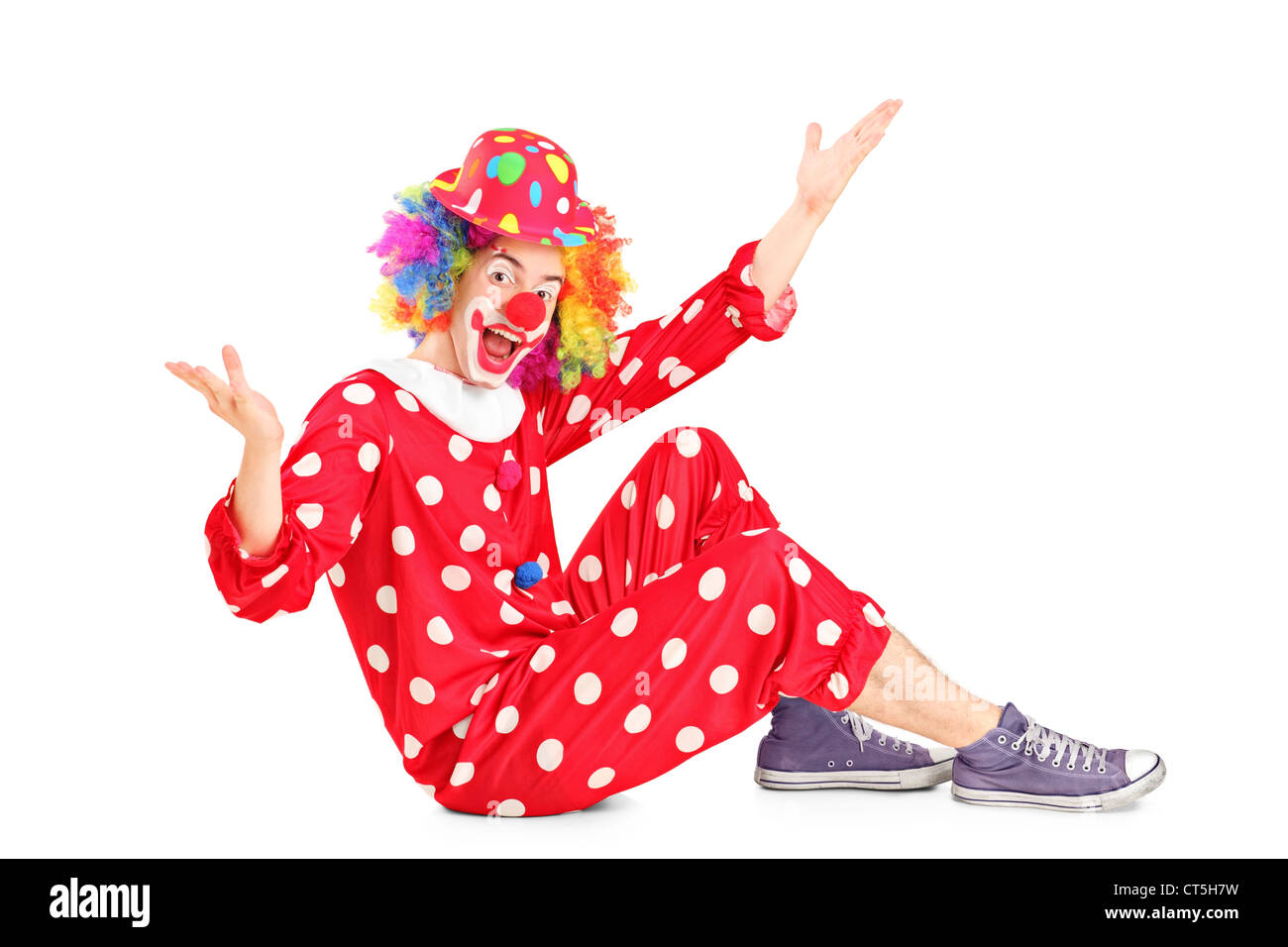 A portrait of a smiling happy clown sitting down isolated on white background - Stock Image