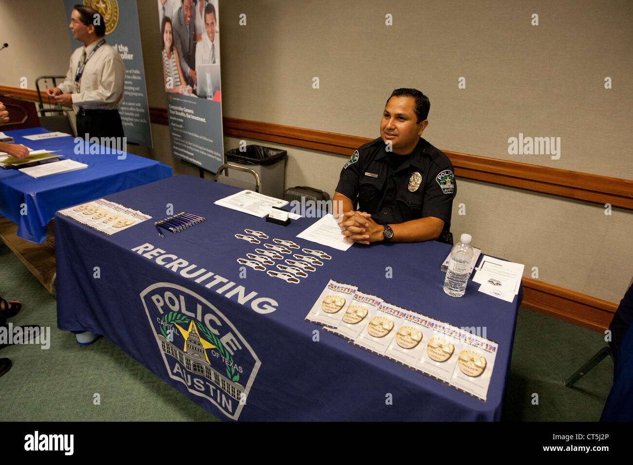 hispanic male police officer sits at recruiting table during a job