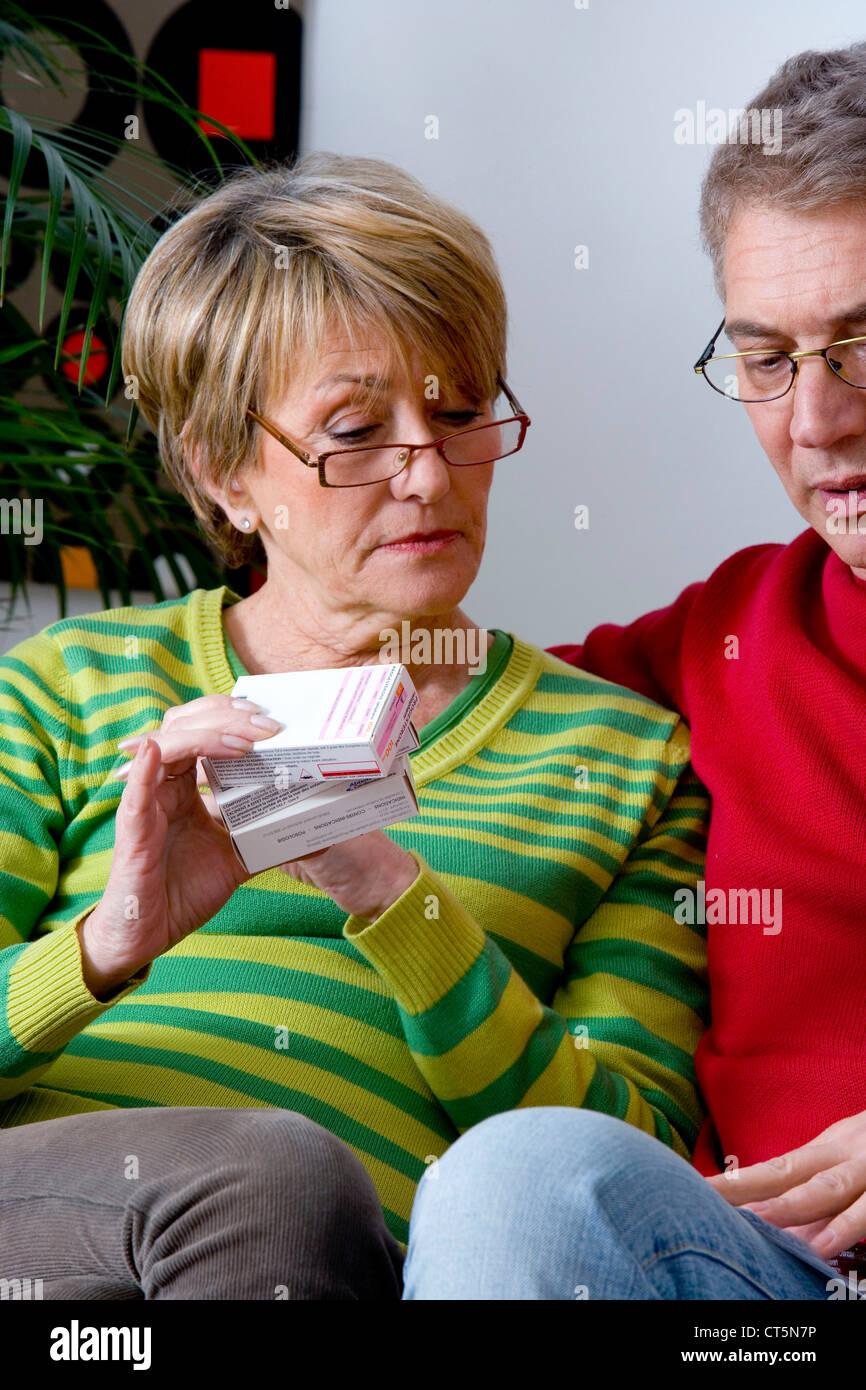 ELDERLY PERSON TAKING MEDICATION - Stock Image