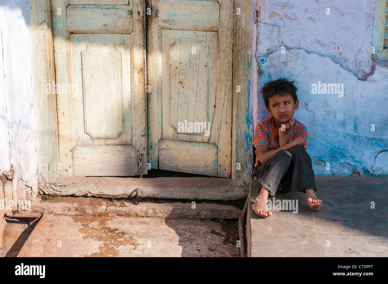 Poor boy sitting in front of a doorway, Pushkar, Rajasthan, India - Stock Image