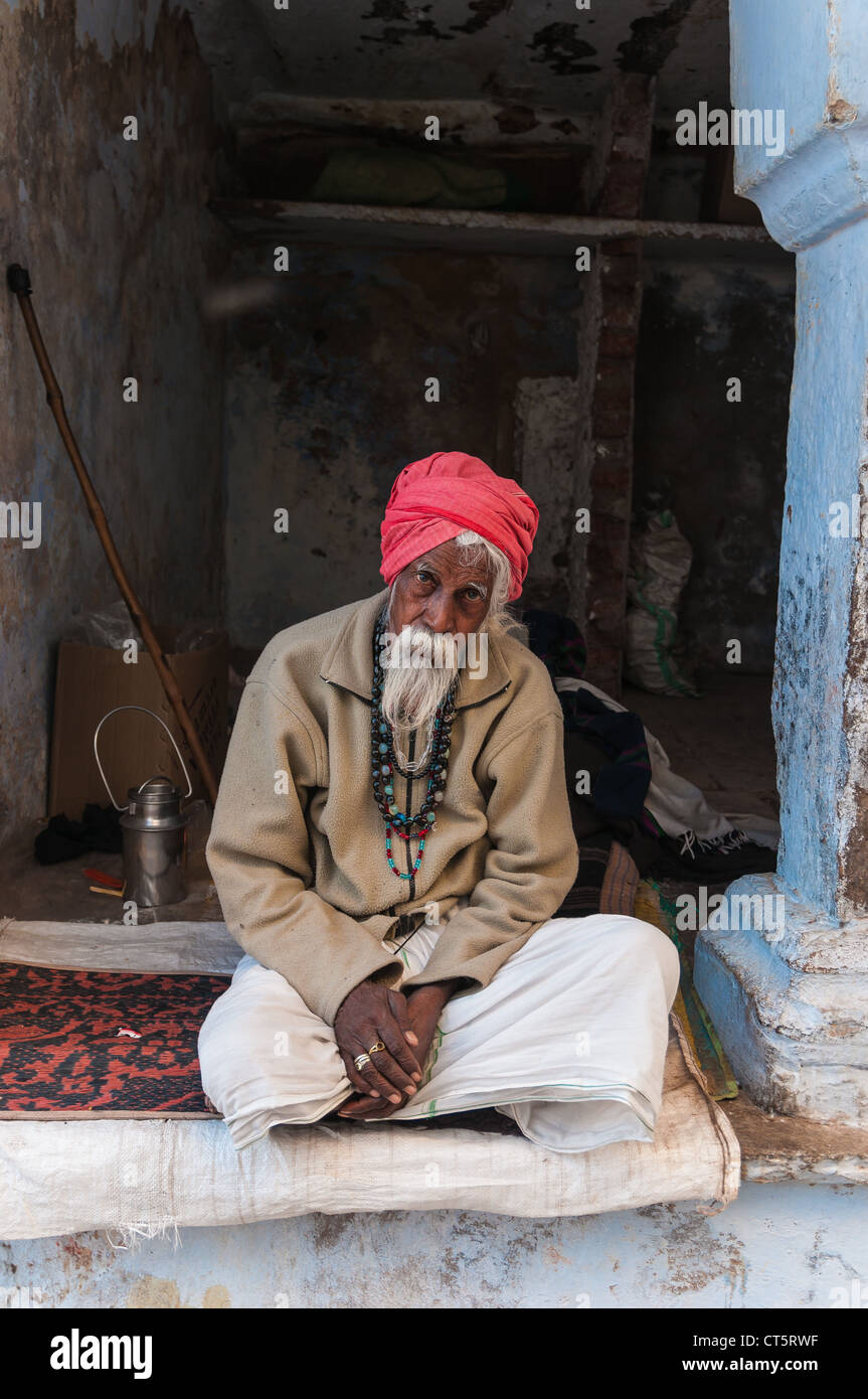 Old Indian man with a red turban, sitting in front of a doorway, Pushkar, Rajasthan, India - Stock Image