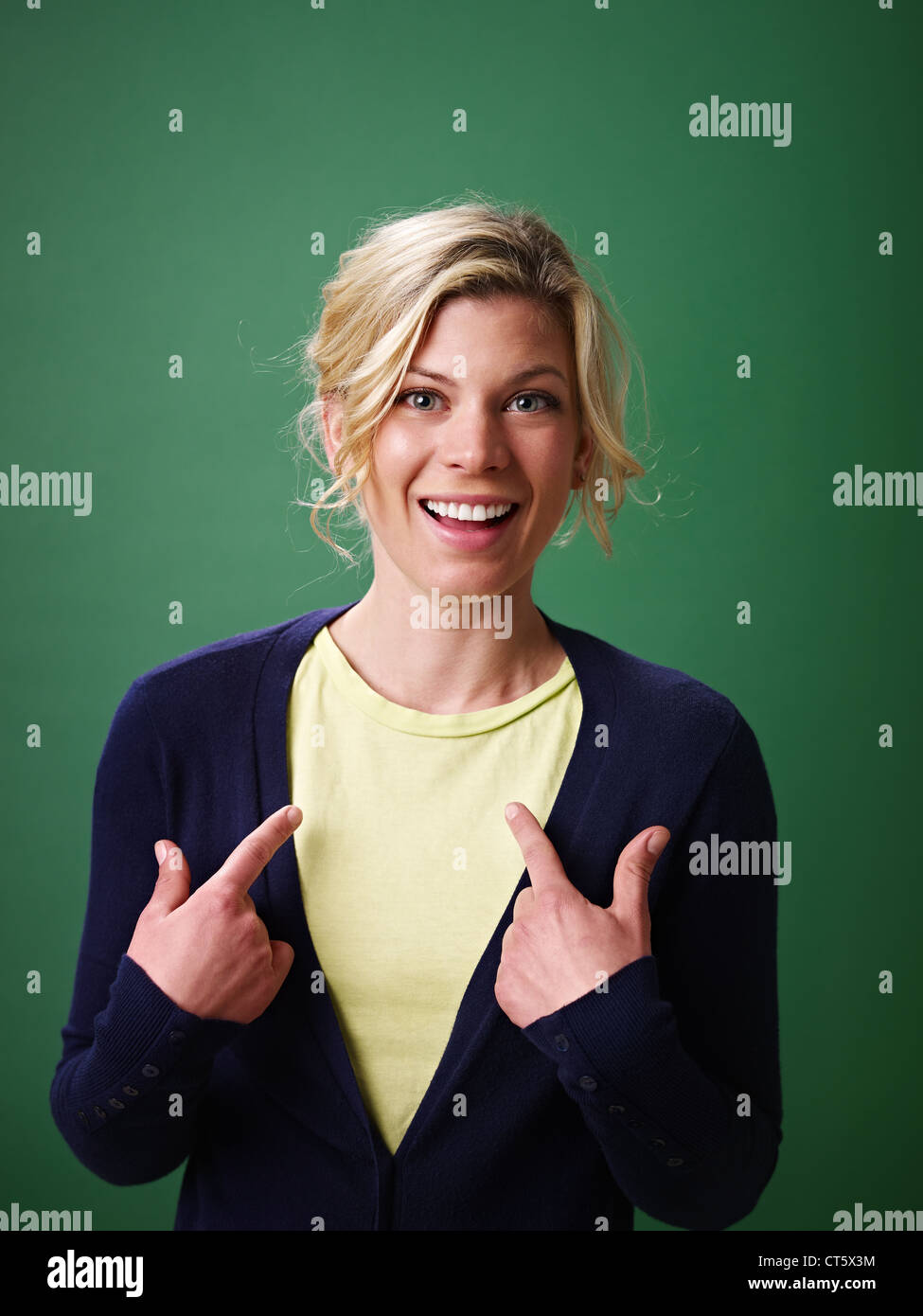 young woman pointing at herself against green background and looking at camera Stock Photo