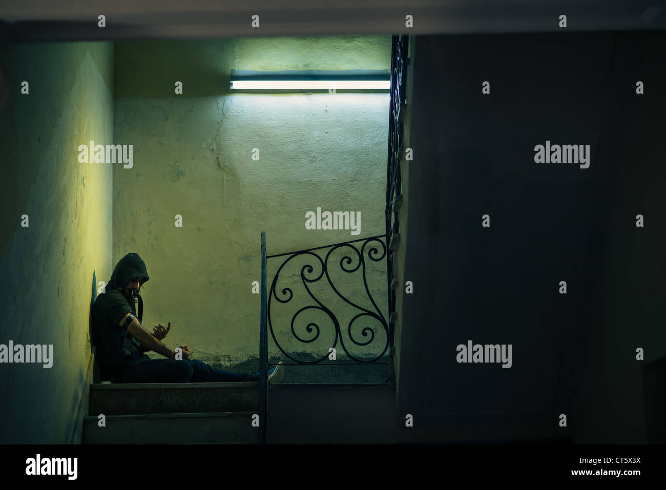 Social issues and drug abuse, young man injecting heroin and sitting on stairs. Copy space - Stock Image