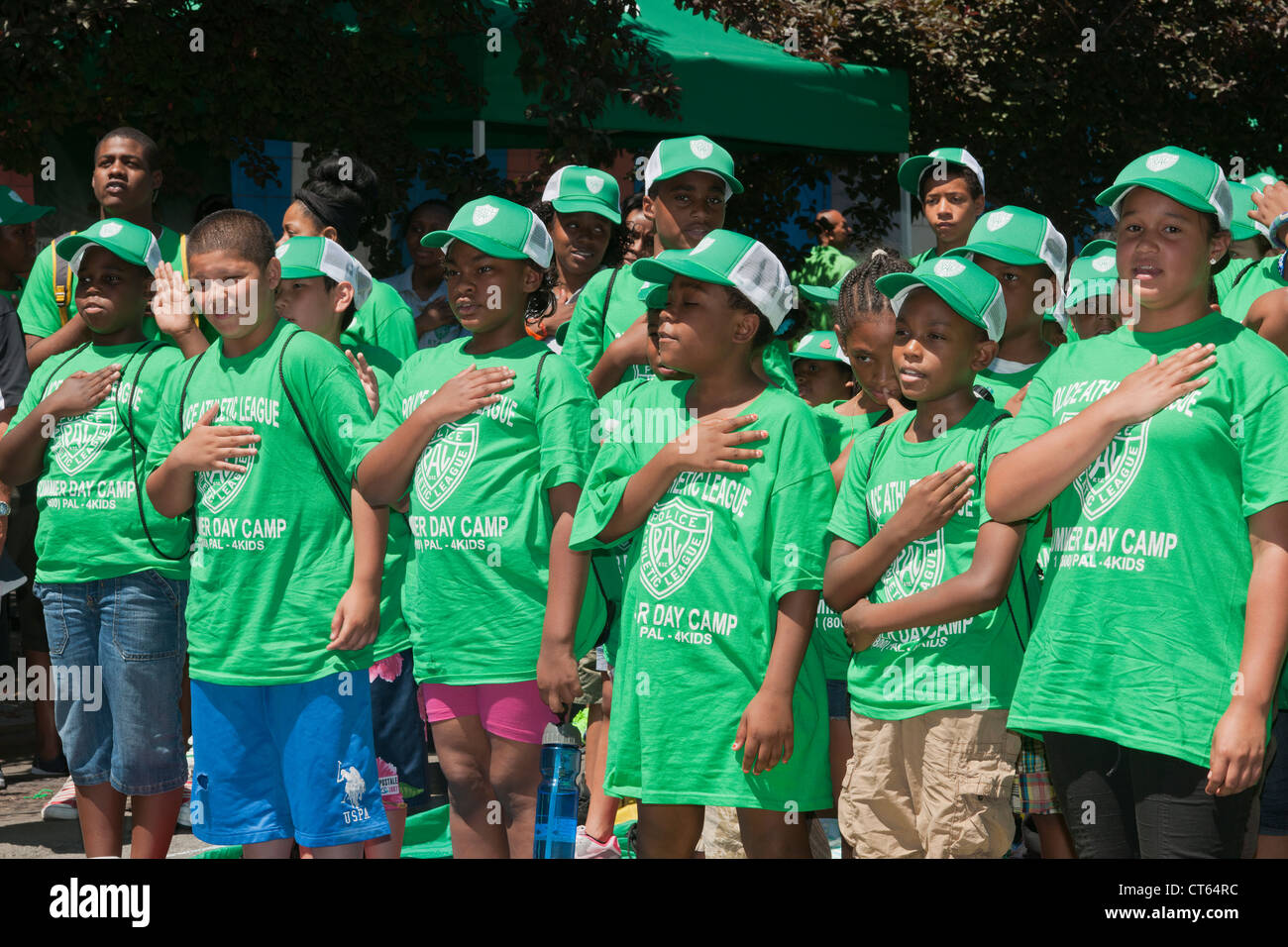 Youngsters recite the Pledge of Allegiance at the opening of the 2012 Summer Play Streets program - Stock Image