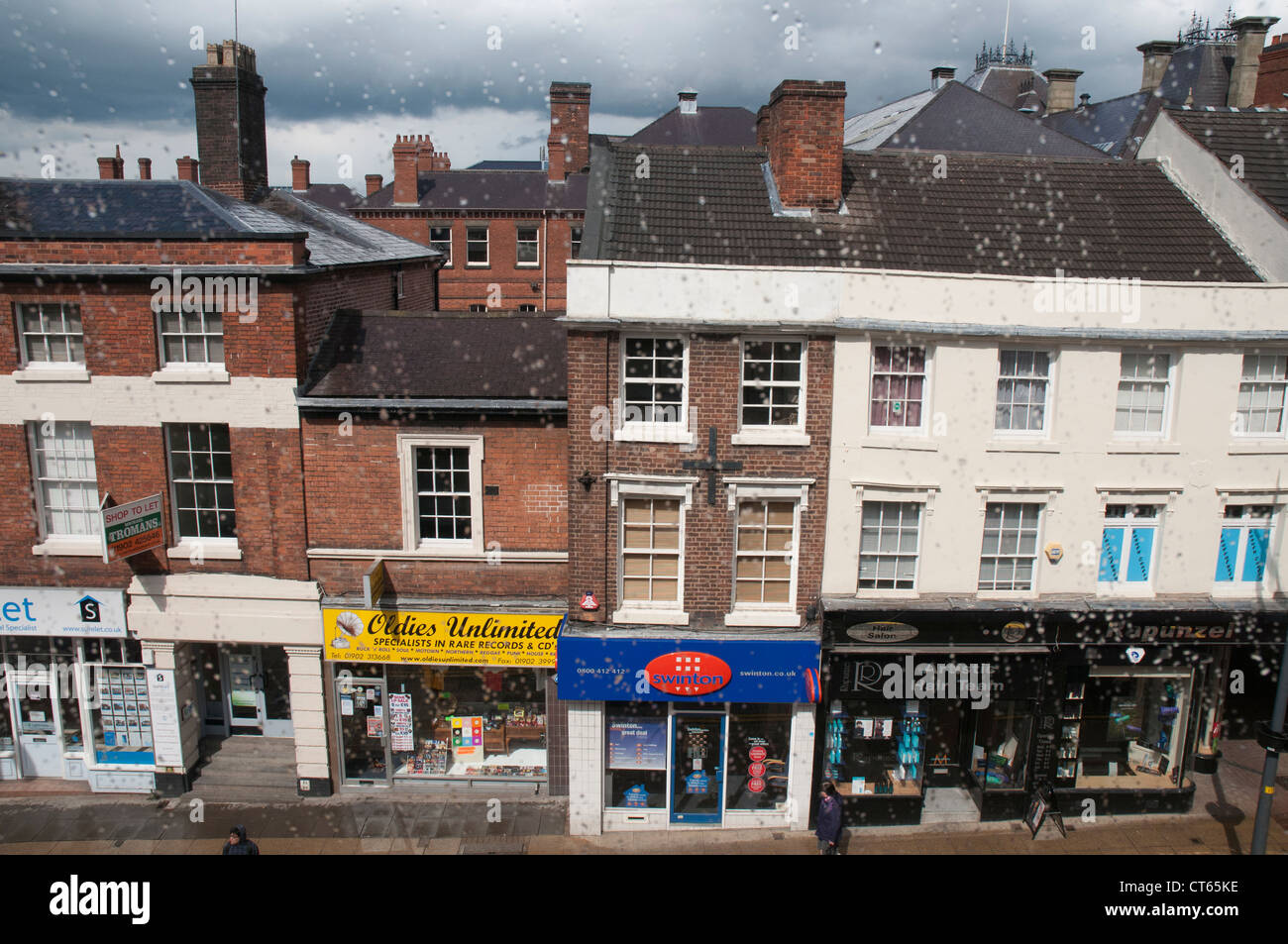 Shopfronts seen through a rain-streaked upstairs window in Wolverhampton, West Midlands - Stock Image