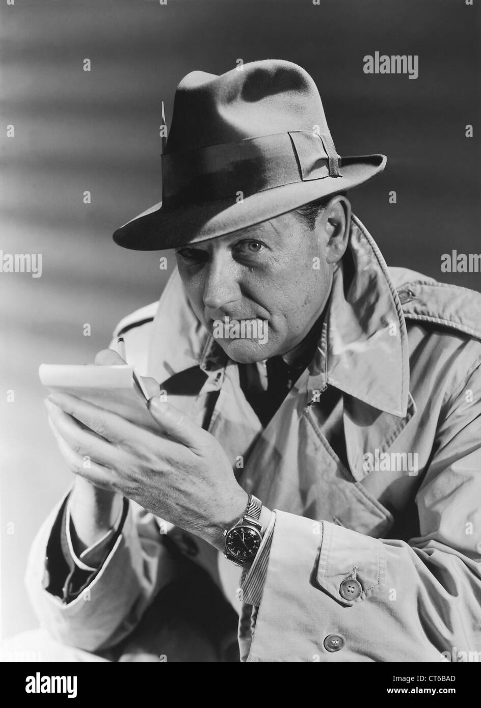 Vintage Detective in an overcoat and hat taking notes - Stock Image