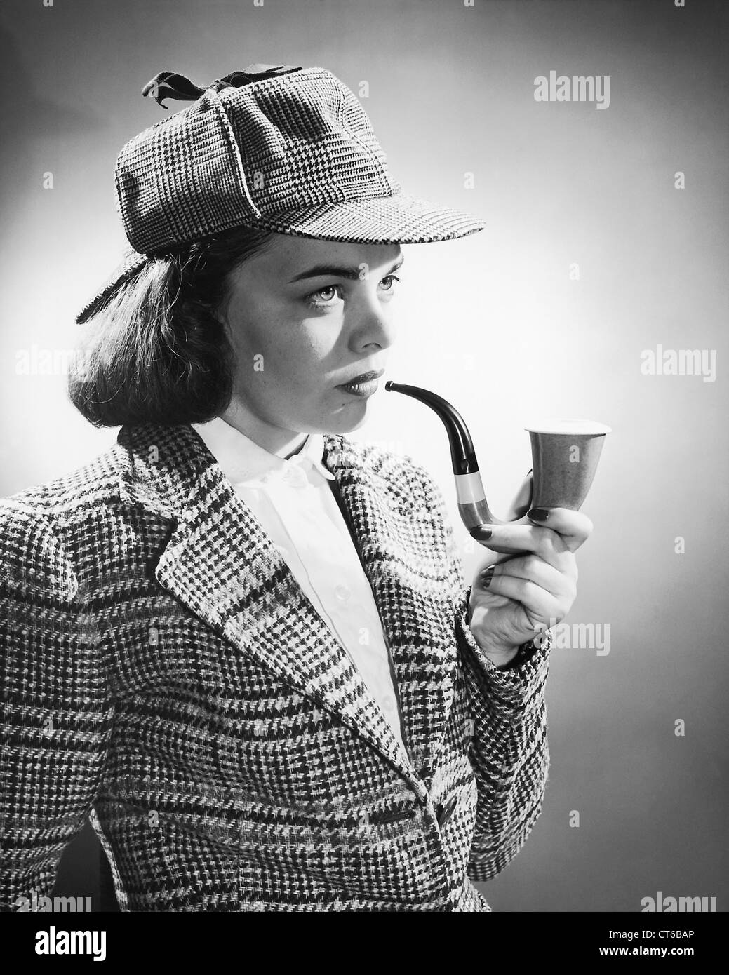 Vintage female Sherlock Holmes detective smoking a pipe and wearing hat - Stock Image