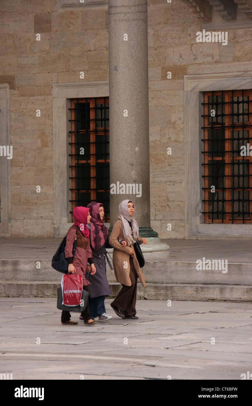 Young muslim women walking in the inner courtyard of Sultan Ahmed Mosque, Sultanahmet, Istanbul, Turkey - Stock Image