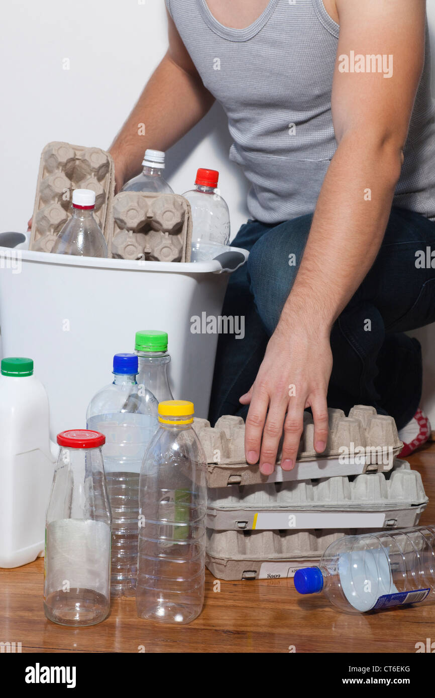Young man putting egg carton and plastic bottles in recycling bin - Stock Image