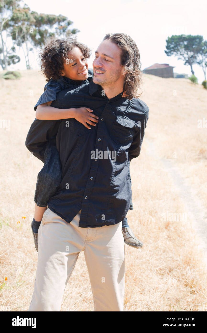Father is piggy backing son in a field. - Stock Image