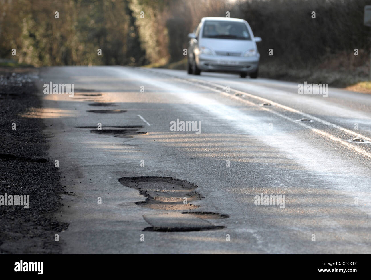 Potholes after winter weather on major roads cause damage to cars - Stock Image