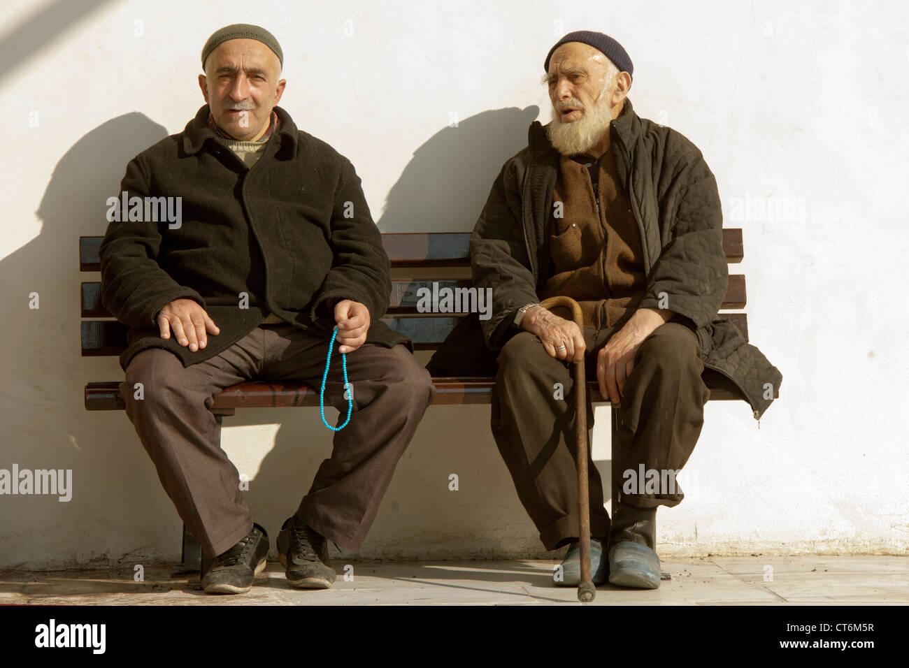 Türkei, Istanbul, Zwei Männer sitzen auf einer Bank vor der Kücük Aya Sofya (Kleine Hagia Sophia), - Stock Image