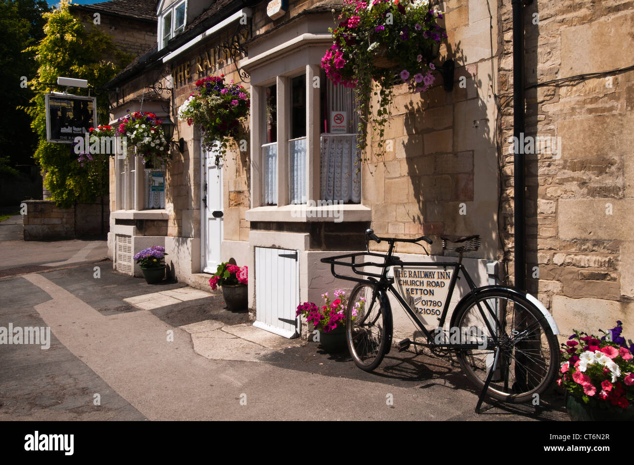 The Railway Inn with colourful hanging baskets and pots in Church Road, Ketton, Rutland, England - Stock Image