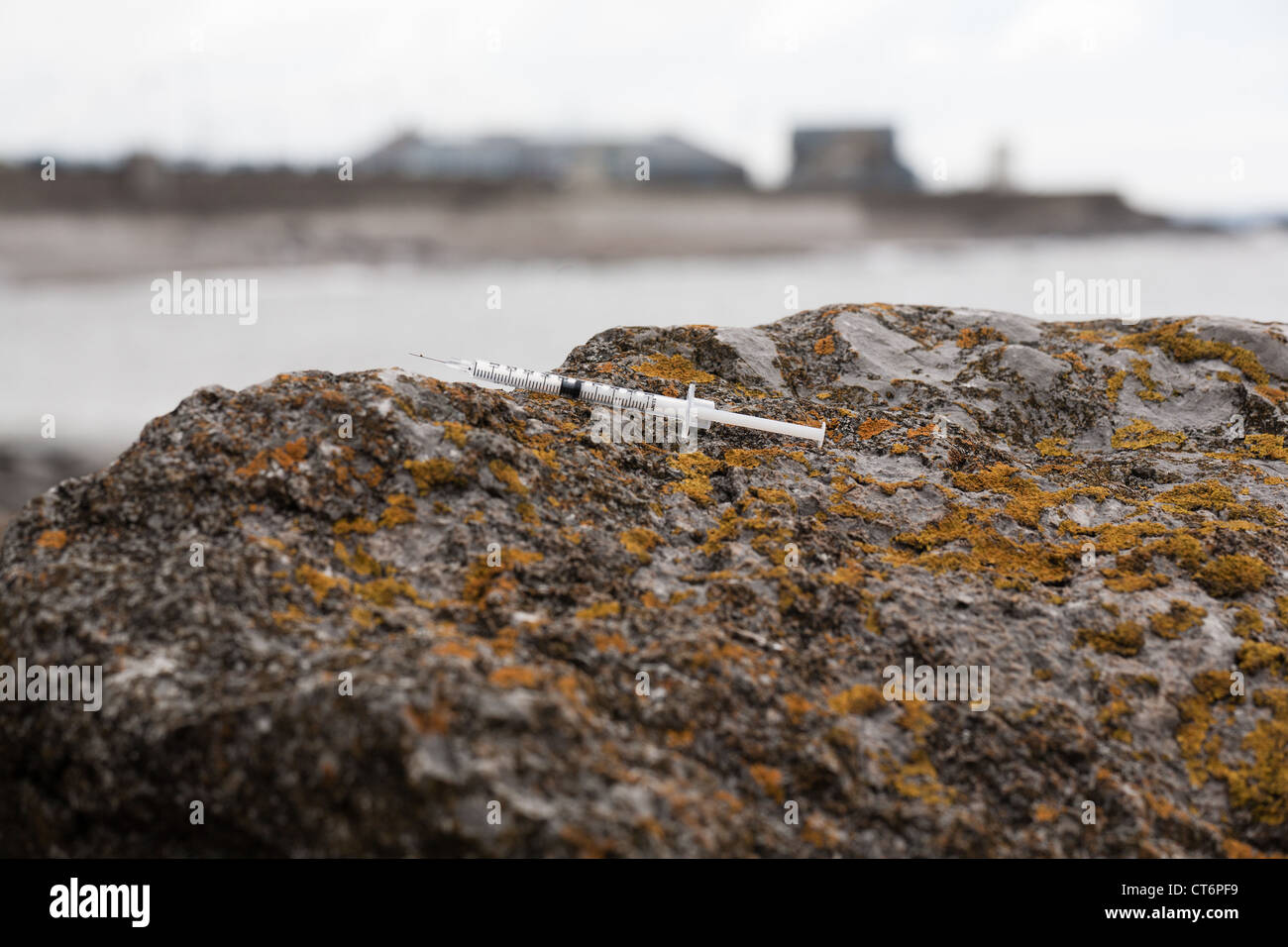 Discarded   Hypodermic  Syringe on a beach - Stock Image