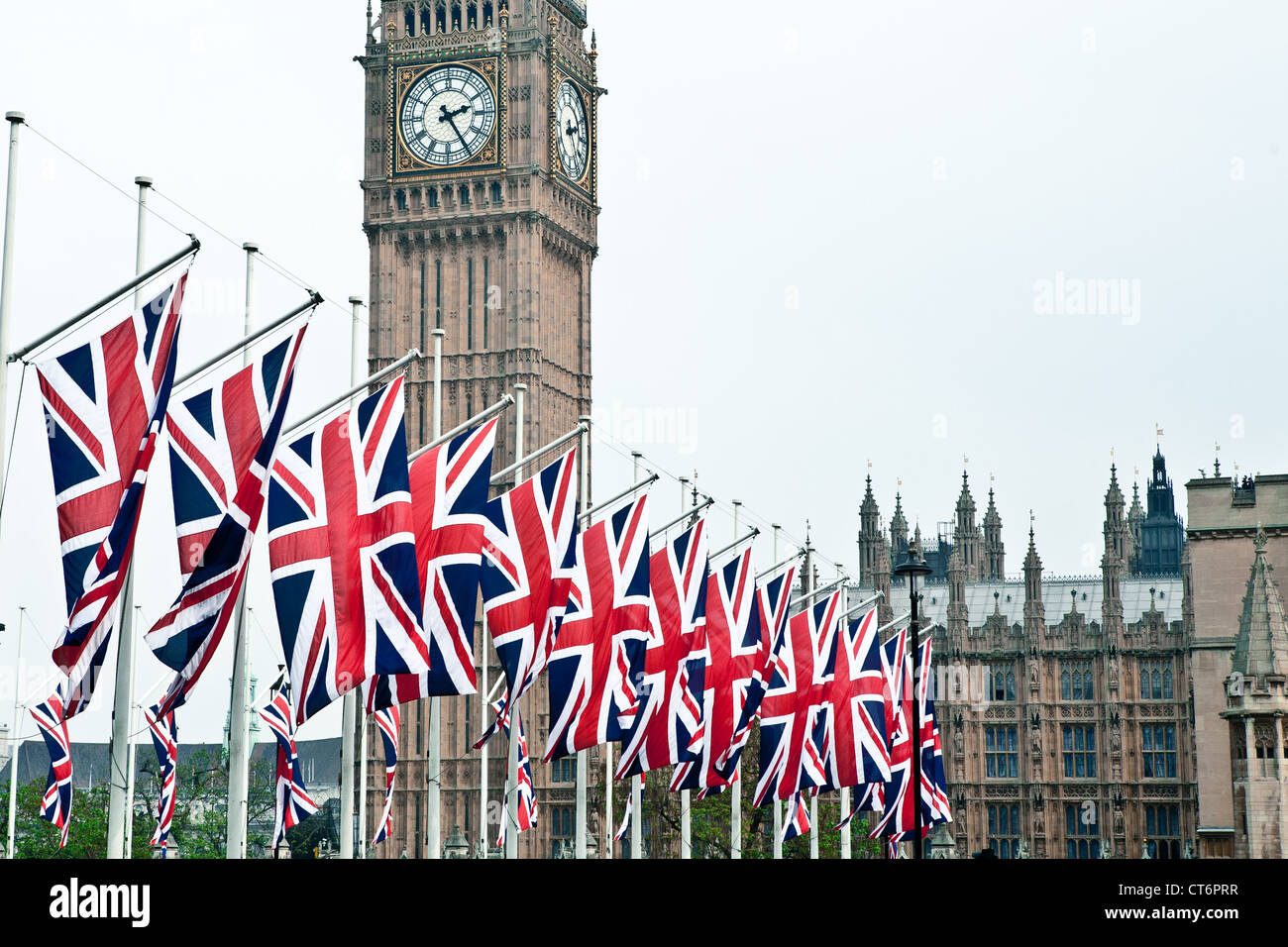 Union Jack flags flying in front of the Big Ben and The Houses of Parliament. Taken on the day of wedding Royal - Stock Image